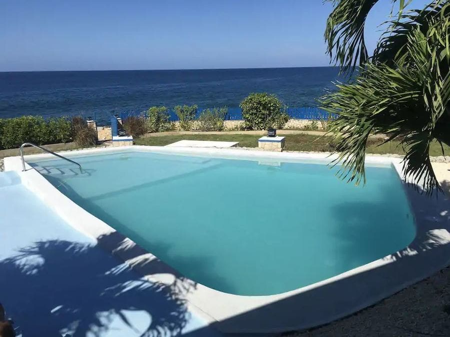 Outdoor pool and beach access at Blue Sky Villa - Photo credit Vrbo